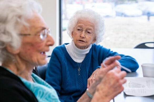 Two seniors talking at a table