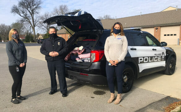Kristan, Angela, and an officer standing beside a cruiser filled with donated clothes