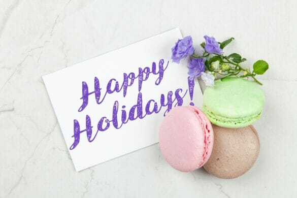 """A card that says """"happy holidays"""" in purple writing with some macaroons around it."""