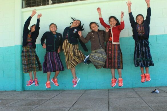 A group of girls jumping n the air, wearing colorful shoes