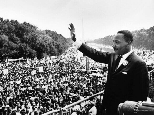 Dr Martin Luther King Jr waving at a crowd of people during a demonstration