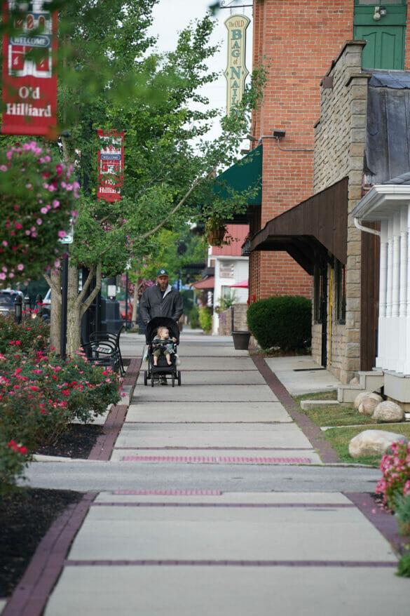 Man walking down sidewalk pushing a stroller