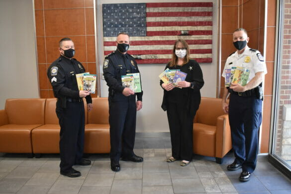Officers holding up books
