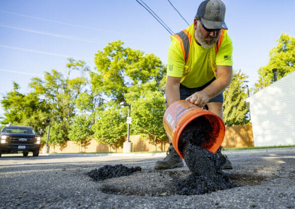 Public service worker pouring tar in a pot hole
