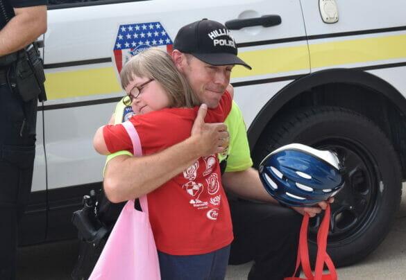 Little girl hugging officer