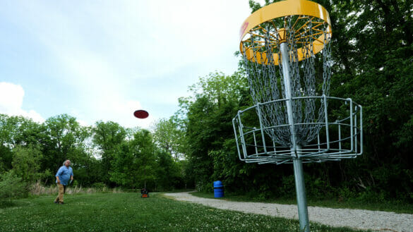 Man throwing frisbee into disc golf net
