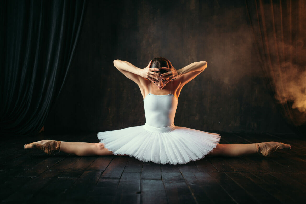 Body flexibility of ballet performer, stretching exercise. Ballerina in white dress sits on a twine on black wooden floor