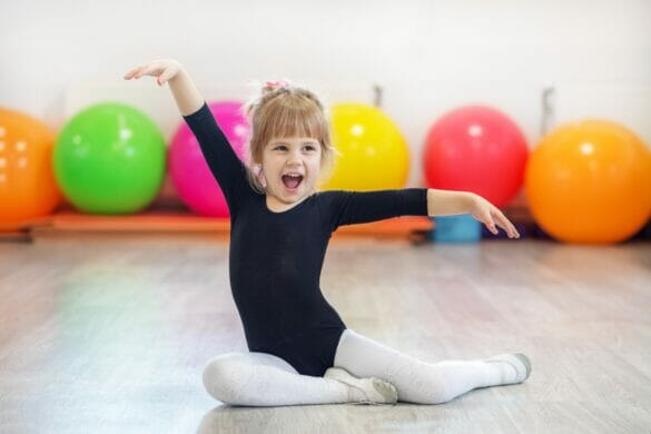 Little preschooler girl learning dance and smiling. The concept of sports, education, hobbies, training and dance.