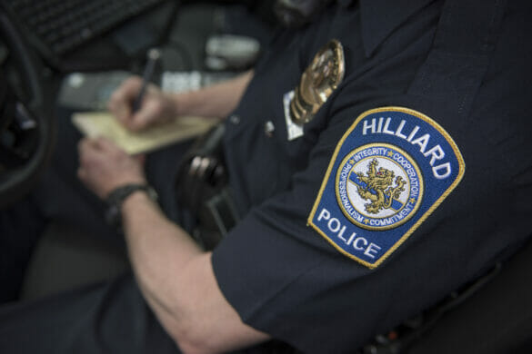 Close up of police badge as officer writes ticket