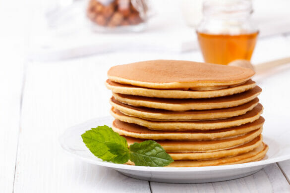 American pancakes stack served with fruits and maple syrup white wooden background family breakfast snack