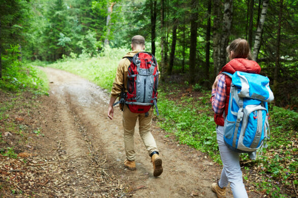 Man and woman with backpacks walking down forest path