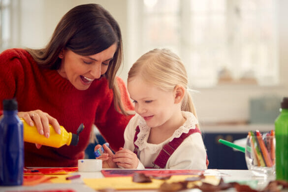 Mother With Daughter At Home Doing Craft And Painting Picture In Kitchen