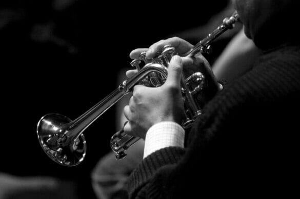 black and white photo of man playing trumpet