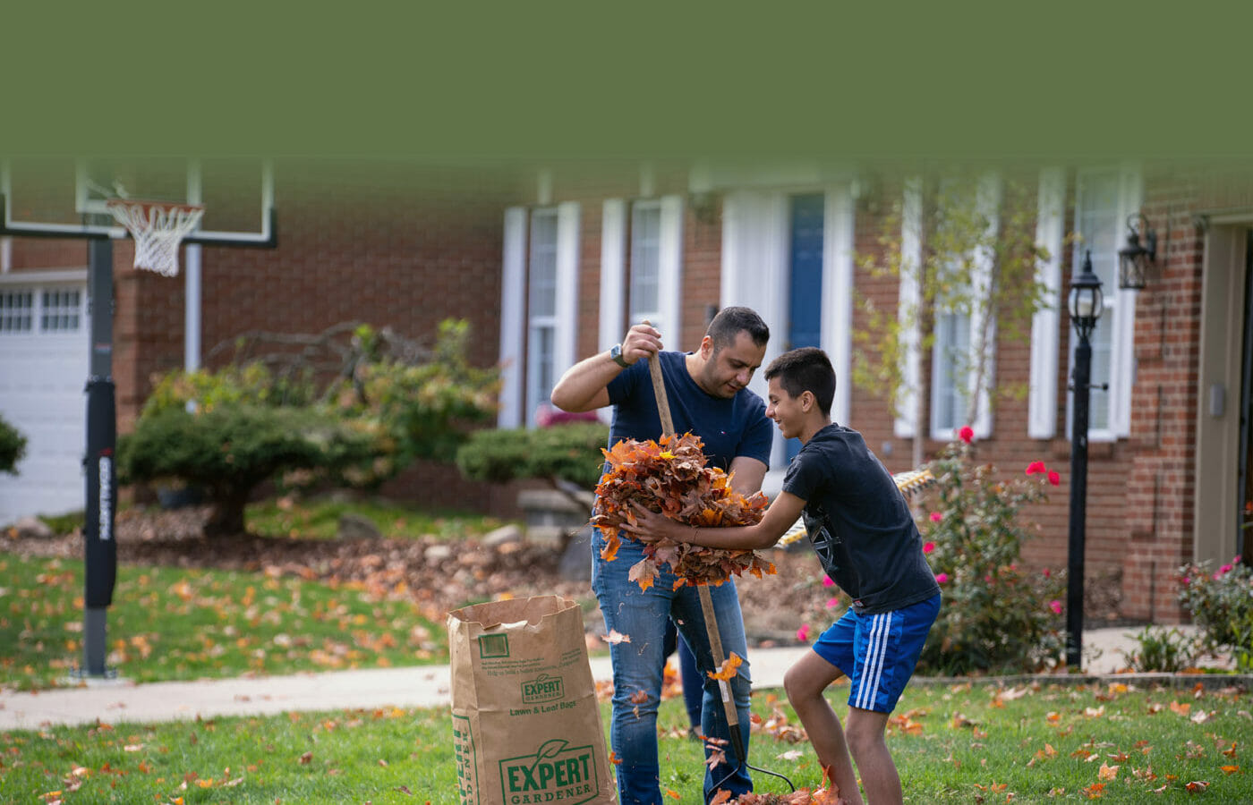 Father and son raking leaves and putting them in bag